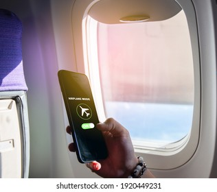 Flight mode concept Slide your finger on the screen to turn on Airplane mode, cut off the smartphone communication near the window on the plane. For the safety of the trip