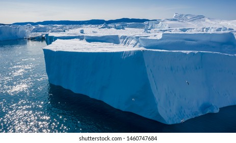 Flight over icebergs and shooting of ices at a short distance. An iceberg surface with thawing traces. Research of a phenomenon of global warming. Millions of tons of floating ice in the World Ocean