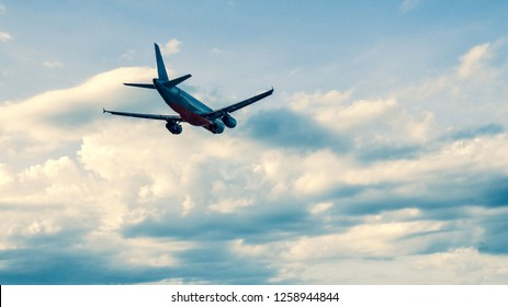 Flight of the plane on the background of a beautiful cloudy sky . copy space for text