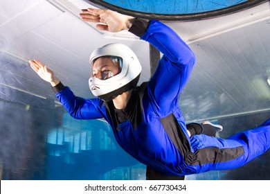 The flight of a pretty young girl in a wind tunnel