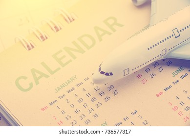 Flight program or plan and travel itinerary concept : White model airplane lands on a desk calendar or flipped calendar, the image depicts a plan for journey or trip / travel that tourist must prepare