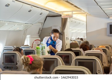 Flight St. Petersburg - Burgas - June 24, 2019: The flight attendant of the airline Iraero serves passengers on the charter flight, offers soft drinks