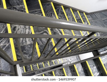 flight of stairs  grey marble staircase with holding hand rail going down with yellow security tape on each stair
