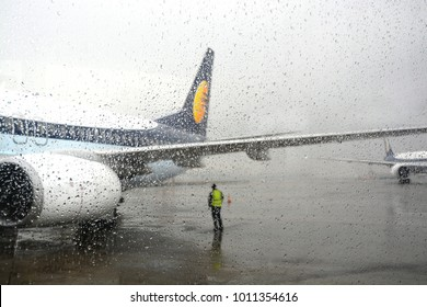 Flight stranded during rain and bad weather in Mumbai airport, India. Airport staff standing looking at the clouds.