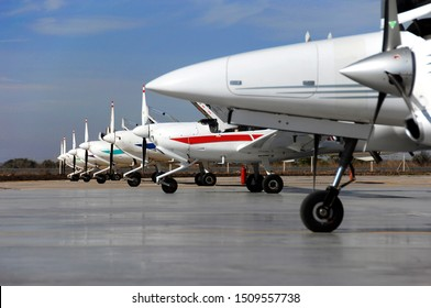 flight training planes on the runway in front of the hangar at the airport