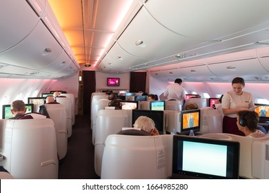 In Flight / United Kingdom - July 27 2015: Qatar Airways Airbus A380 Business Class cabin with reverse herringbone seats. Skytrax five stars airline with hub in Doha. Qatari flight attendant.