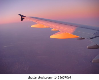 In Flight View Of Airplane Wing With Low Angled Sun Light Over Hazy Air