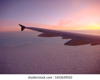 In Flight View Of Airplane Wing With Low Angled Sun Light Over Clouds