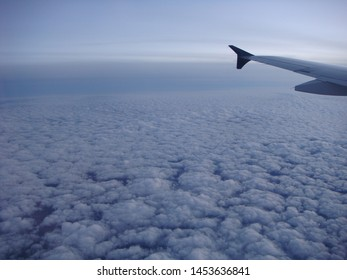 In Flight View Of Airplane Wing Over Clouds