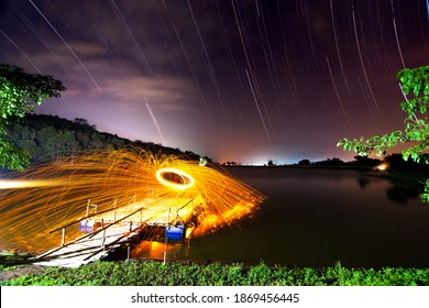 Flinging fire in the lake at thailand ,night scene of star tail on background.