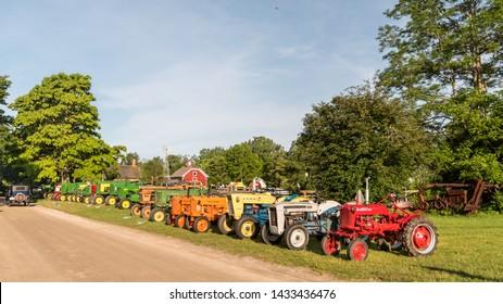 FLINT, MI/USA - JUNE 22, 2019: A row containing International Harvester and John Deere tractors at the Sloan Museum Auto Fair car show, held at Crossroads Village, near Flint, Michigan.