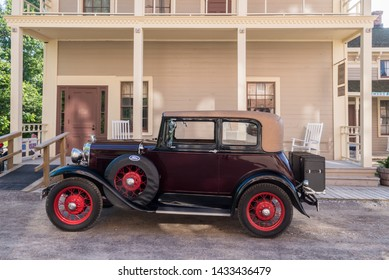 FLINT, MI/USA - JUNE 22, 2019: A vintage Ford coupe car and Attica Hotel at the Sloan Museum Auto Fair car show, held at Crossroads Village, near Flint, Michigan.