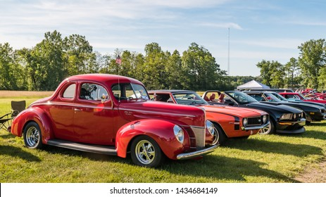 FLINT, MI/USA - JUNE 22, 2019: A row of classic cars, including a 1940 Ford Deluxe, at the Sloan Museum Auto Fair car show, held at Crossroads Village, near Flint, Michigan.