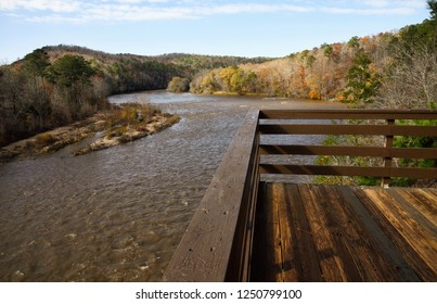 Flint River at Sprewell Bluff Park in Thomaston Georgia USA cutting its way through river bluffs and rock outcrops on its way to the Gulf of Mexico. Autumn leaf color in the surrounding hills.