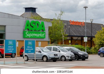 Flint, UK: May 1, 2018: Asda & Sainsbury's who announced a potential merger with no store closures are neighbours in the Welsh town Flint.  Asda's logo on their Flint store & Sainsbury's at the side.