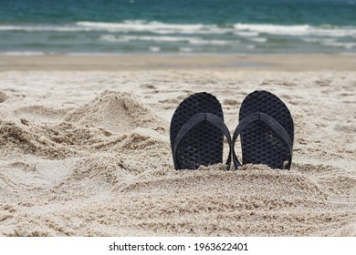 Flip flops in the beach. Slippers embed in sand beach.