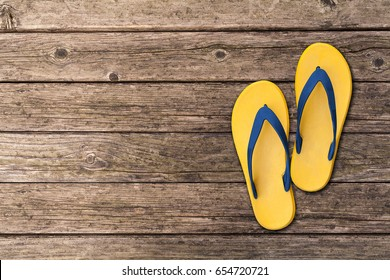 Flip flops isolated on wooden floor. Top view and copy space. Slippers yellow