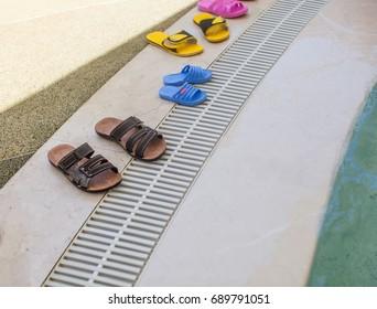 A lot of flip flops near a swimming pool