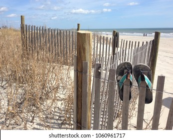 Flip flops on a beach fence.