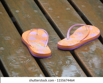 Flip flops in the rain. Orange and pink on timber decking.