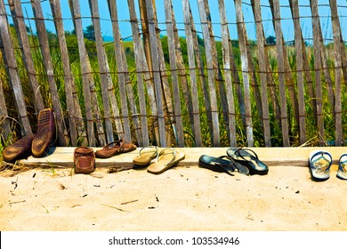 Flip flops and sandals lined up at the beach.  Old, well worn, not new