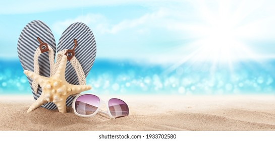 Flip flops, starfish and sunglasses on sunny sea beach with copy space. Travel vacation concept
