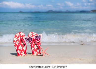 Flip flops and sunglasses on white sandy tropical beach, Summer vacation and travel concept