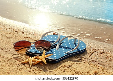 Flip flops, sunglasses and starfishes on beach sand