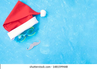 flip flops and swimming goggles near the pool, Santa Claus hat, Christmas vacation, mustache and swimming glasses by blue background. Christmas background for pool or fitness club. happy new year