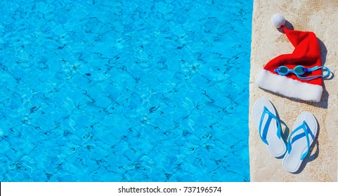 flip flops and swimming goggles near the pool, Santa Claus hat, Christmas vacation, sandals and swimming glasses by water, slippers and pool goggles near swimming pool