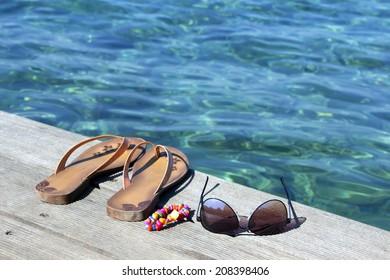 Flip-flop, sunglasses and  bracelets on wooden dock near the sea