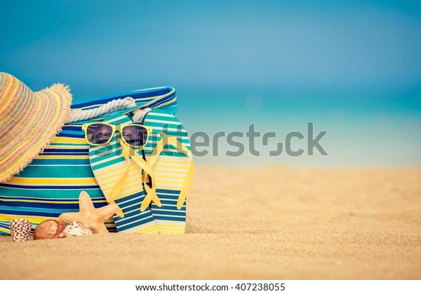 Flip-flops y bolsa en playa de arena contra el azul del mar y el cielo fondo. Concepto de vacaciones de verano