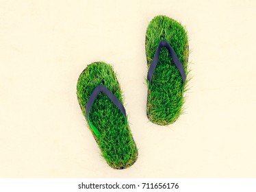 Flip-flops made of green artificial grass on the marble background. Save the nature, environment, ecology, traveling concept