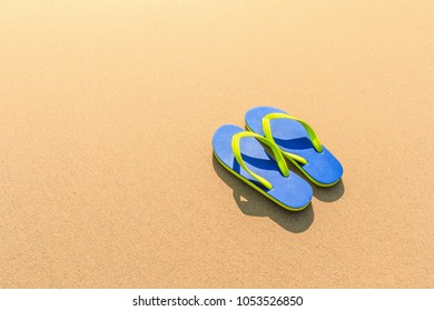 Flip-flops on the beach - Green and Blue Flip-flops on the brown sand beach background. Tropical vacation concept and copy space