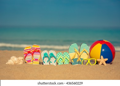 Flip-flops on sandy beach against blue sea and sky background. Summer vacation concept
