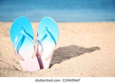 Flip-flops in sand on beach. Space for text