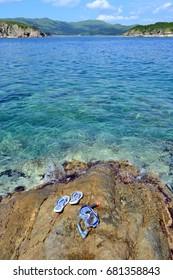 Flip-flops, sky, rocks, sea, clear water. Gamov Peninsula. Primorye. Russia.