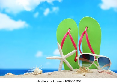 Flip-flops,sunglasses with starfish on beach