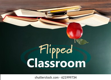 Flipped classroom concept. Inversed books with apple on blackboard background