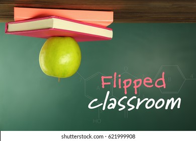 Flipped classroom concept. Inversed books and apple on blackboard background