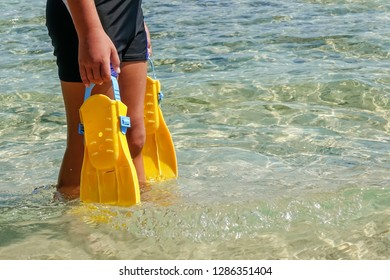 .Flippers in the hands of a man on the Mediterranean coast.