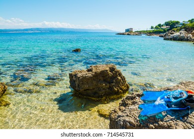 Flippers, mask and snorkel ona rocks by the sea in Sardinia, Italy