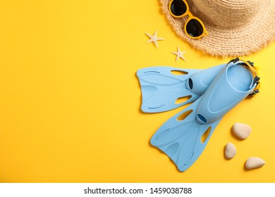 Flippers, straw hat, sunglasses and starfishes on yellow background