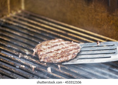 Flipping a hamburger patty on a hot barbecue grill