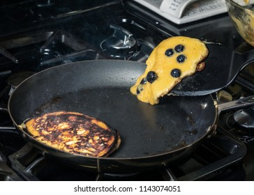 Flipping paleo pancakes in a frying pan with hot butter