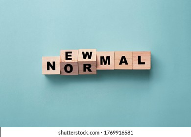 Flipping wooden block cubes for new normal wording on green background. The world is changing to balance it into new normal include business , economy , environment and health.