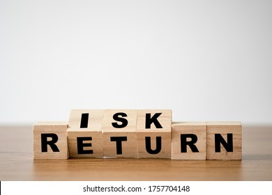 Flipping of wooden cubes block which print screen risk and return wording. Investment concept about balance between risk and return.