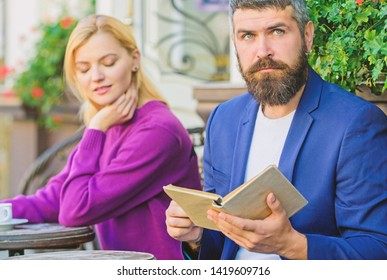Flirt and date. Meeting people with similar interests. Man and woman sit terrace. Literature common interest. Find person with common interest. Same taste in literature. Girl interested what he read.