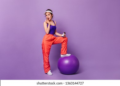 Flirtatious girl in sporty outfit posing on purple background with fitball. Woman in orange pants is enjoying chocolate