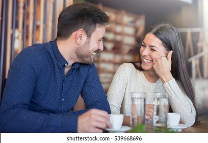 Flirting in a cafe. Beautiful loving couple sitting in a cafe enjoying in coffee and conversation. Love and romance.